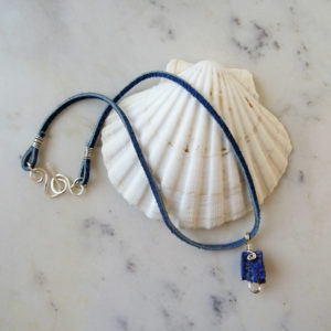 Photo of rough-denim-lapis-pendant-handmade-by-Calico-Rose-Studio. Raw-stone-pendant displayed on a scallop shell.