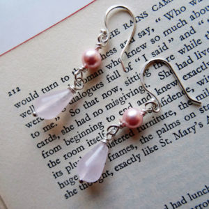 Photo of Rose-quartz-drop-earrings-handmade by Calico-Rose-Studio displayed on an open book
