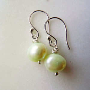 Photo of pastel green pearl-earrings-handmade by Calico Rose Studio displayed on table top