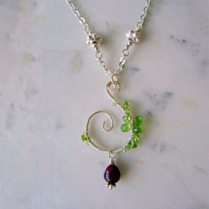 Photo of peridot-pendant-necklace-with-ruby-dangle handmade by Calico Rose Studio in the UK