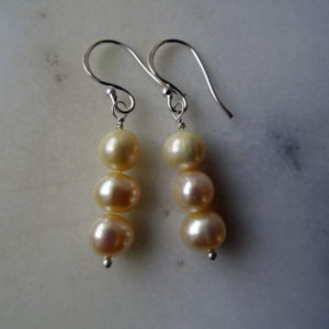 Photo of triple-cream-pearl-earrings-handmade by Calico Rose Studio on table top